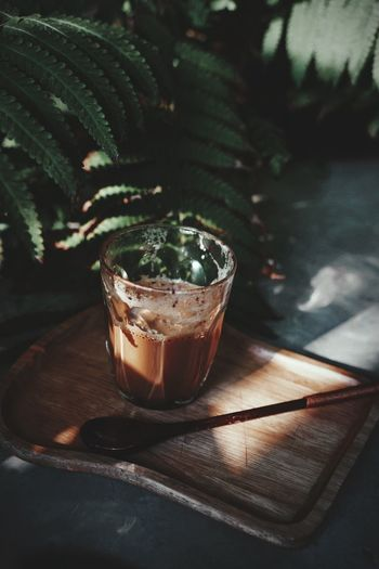 High angle view of drink in glass by of potted plant on table