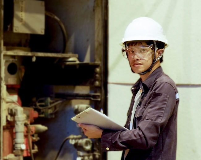 One Person Occupation Hardhat  Waist Up Men Holding Helmet Standing Portrait Real People Glasses Headwear Working Eyeglasses  Hat Adult Indoors  Mature Adult Looking At Camera