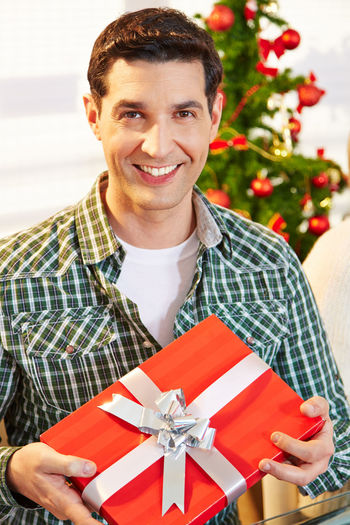 Portrait Of Smiling Man Holding Christmas Gift While Standing At Home