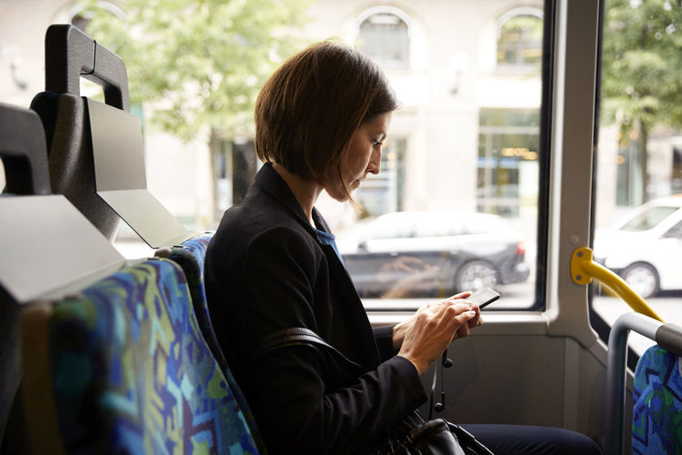Man using mobile phone while sitting in bus