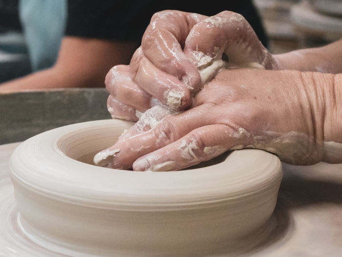 Cropped Hands Of Man Shaping Mud On Pottery Wheel