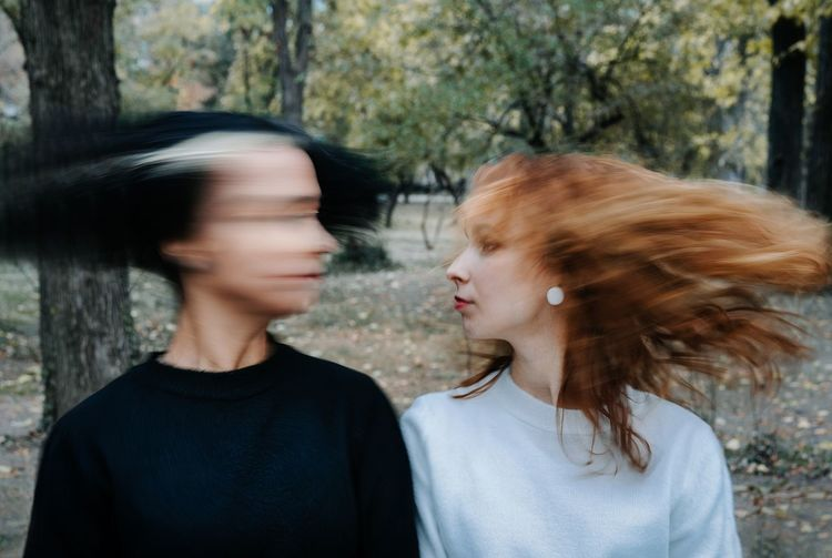 Lesbian Couple Shaking Heads While Standing Against Trees In Park