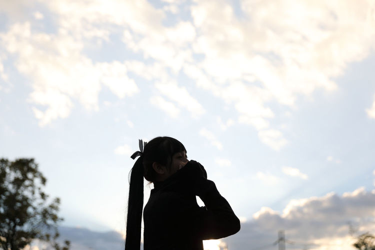 Side view of woman standing against sky