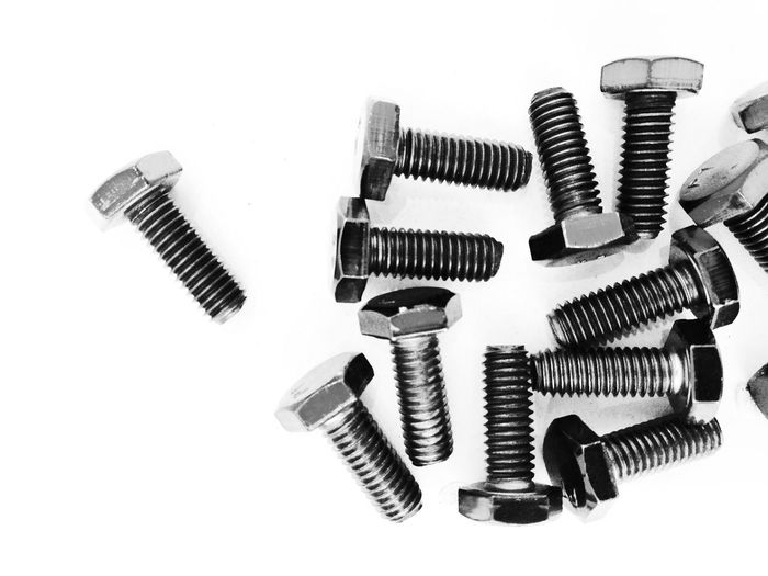 Close-Up Of Nut Bolts On White Background
