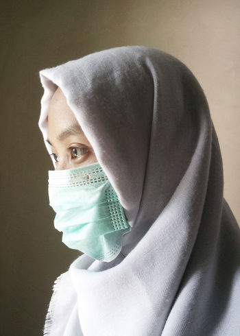 Young woman with health mask close up Close-up Day Headshot Healthcare And Medicine Hijab Human Face Hygiene Indoors  Looking At Camera One Person People Portrait Protection Real People Scarf Side View Studio Shot Surgical Cap Surgical Mask White Background Women Young Adult Young Women