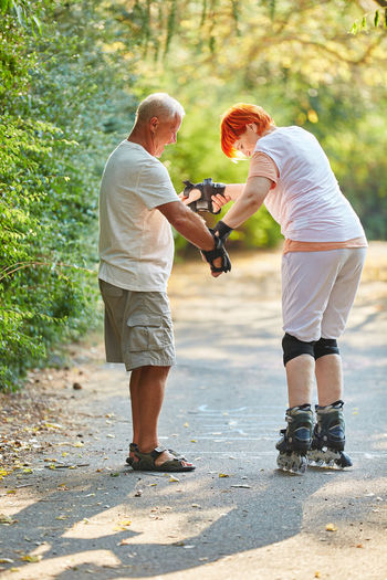 Side View Of Senior Man Assisting Woman In Roller Skating On Road Against Trees At Park