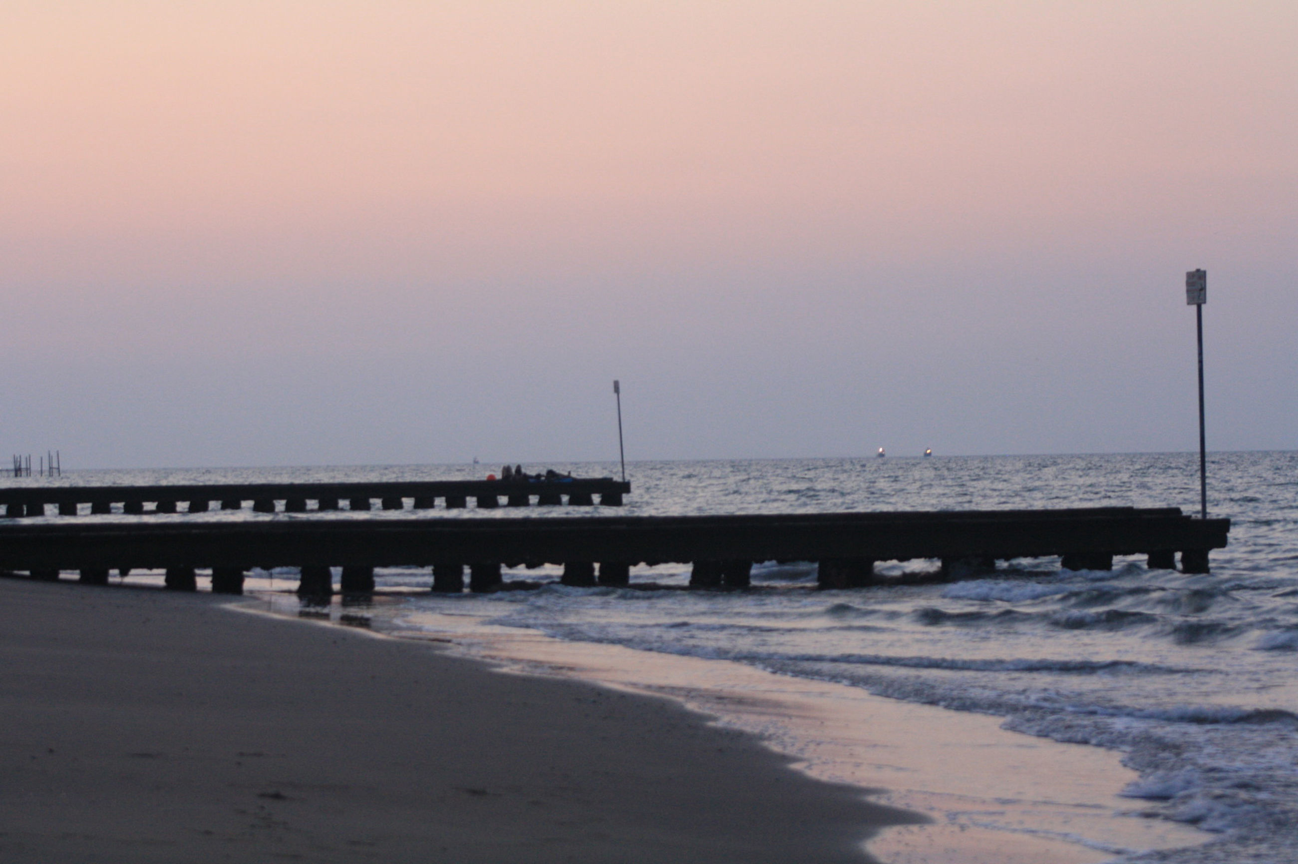 sea, water, horizon over water, sunset, beach, tranquil scene, scenics, tranquility, shore, pier, beauty in nature, copy space, nature, sky, clear sky, idyllic, silhouette, sand, wave, dusk