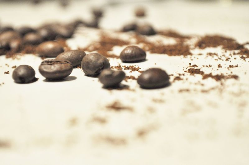Close-up of coffee beans on sand