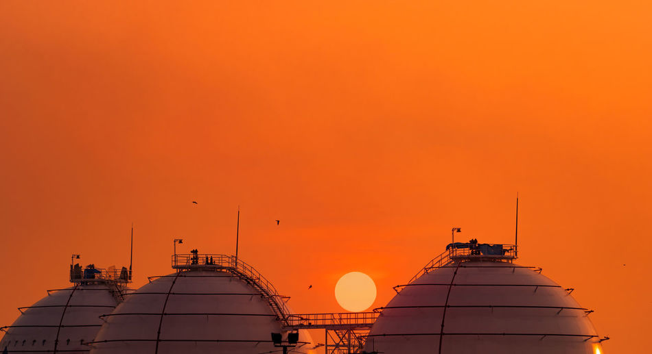 Industrial gas storage tank on orange sunset sky. lng or liquefied natural gas storage tank.