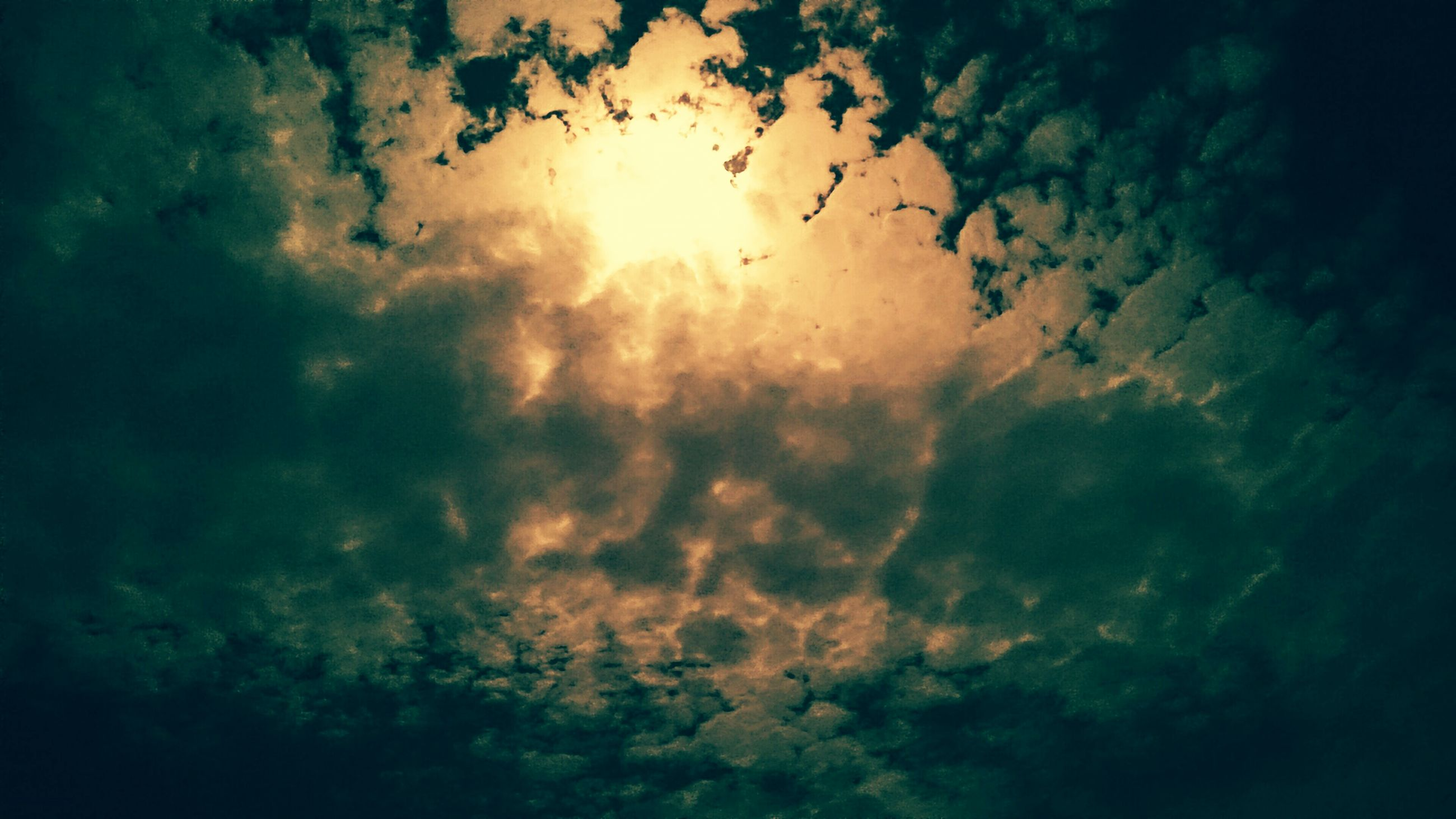 sky, cloud - sky, sun, low angle view, sunset, beauty in nature, tranquility, scenics, cloudy, nature, tranquil scene, sunbeam, sunlight, cloud, silhouette, idyllic, weather, outdoors, dramatic sky, no people