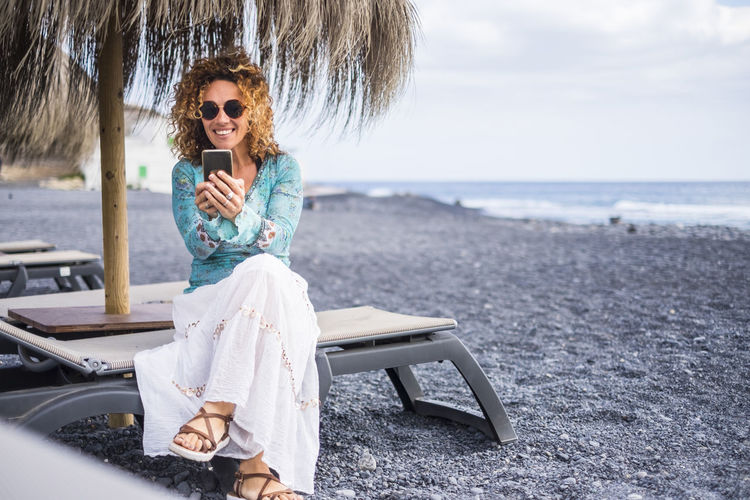 Full length of young woman using mobile phone while sitting at beach