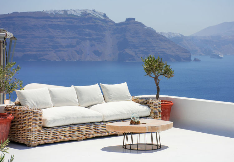 Chairs and table by swimming pool by sea against mountain