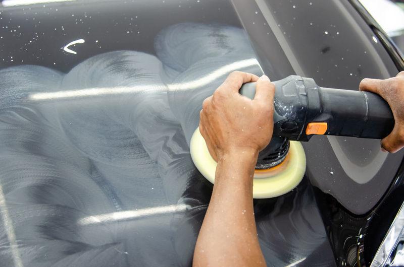 Cropped hands of man polishing car