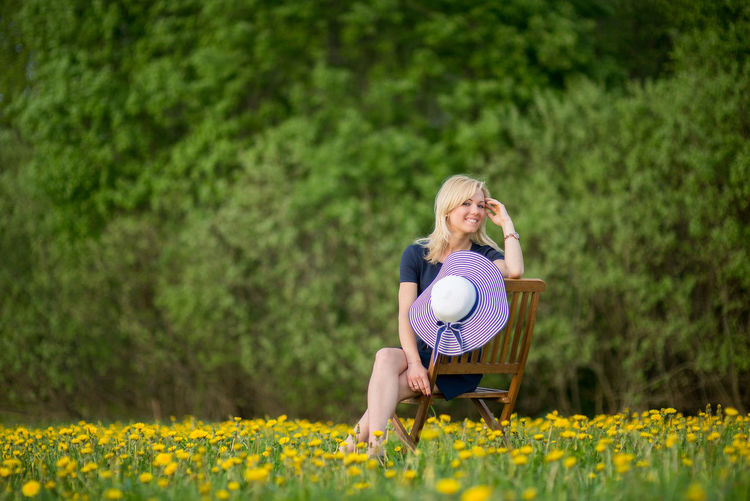 Portrait of young woman with hat sitting on chair at dandelion meadow