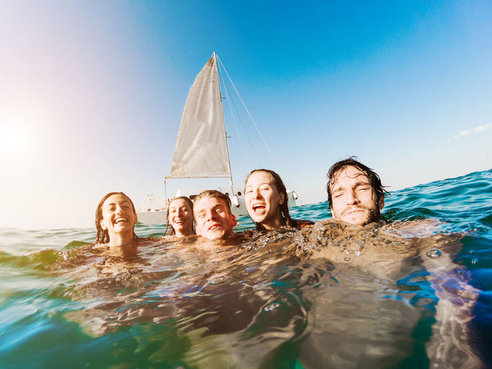Portrait Of Friends Swimming In Sea Against Blue Sky