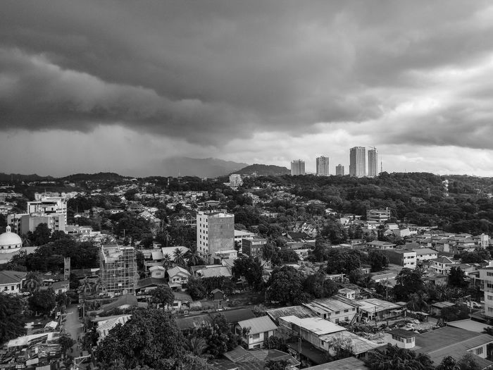 High angle view of buildings in city against storm clouds