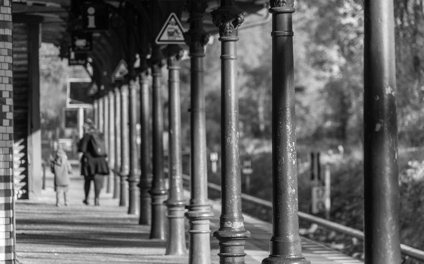 Rear view of people walking on railroad station platform