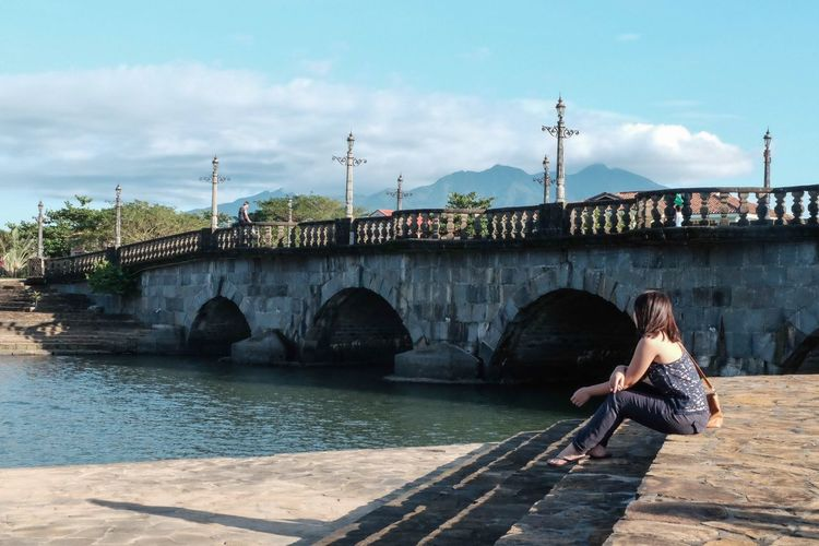 Side view of woman sitting on promenade besides bridge by river