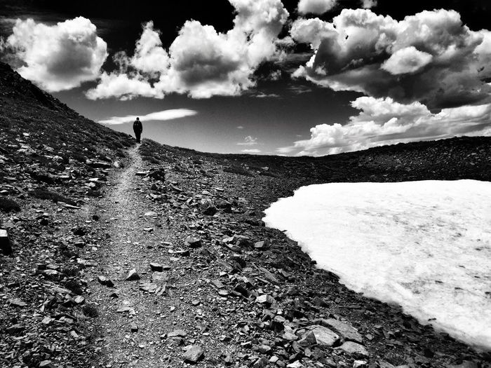 Rear view of hiker walking on dirt road against cloudy sky