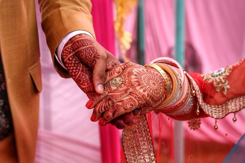 Cropped Image Of Couple Holding Hands At Wedding Ceremony