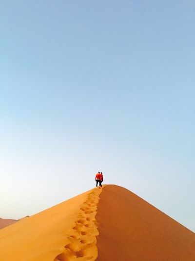 People walking on desert against clear sky