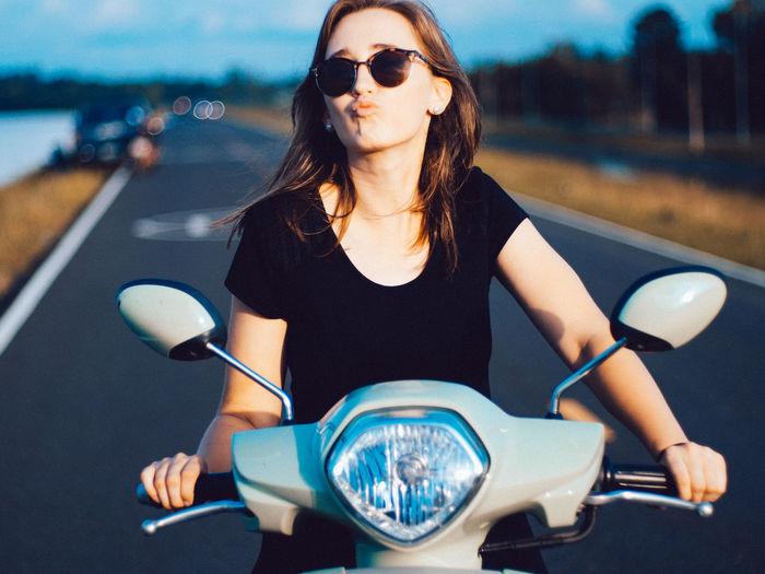 Young woman wearing sunglasses riding motor scooter
