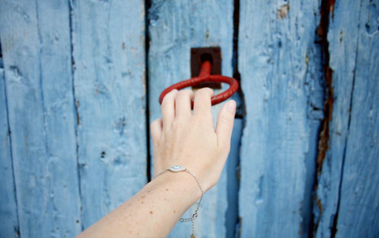 Close-Up Of Hand With Key In Door