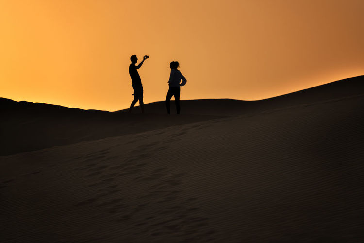 Silhouette men standing on desert against sky during sunset