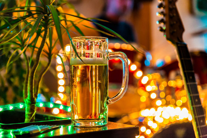 Beer Glass On Table Against Lighting Decorations