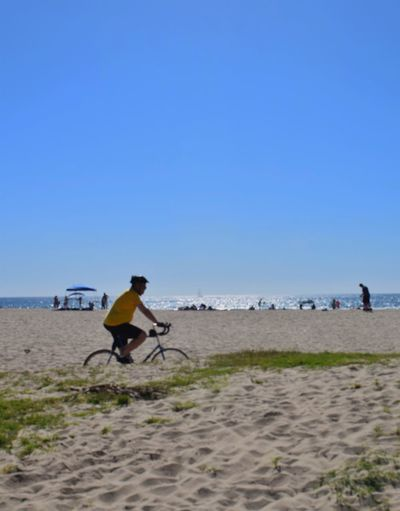 Side View Of Man Riding Bicycle At Beach Against Clear Sky