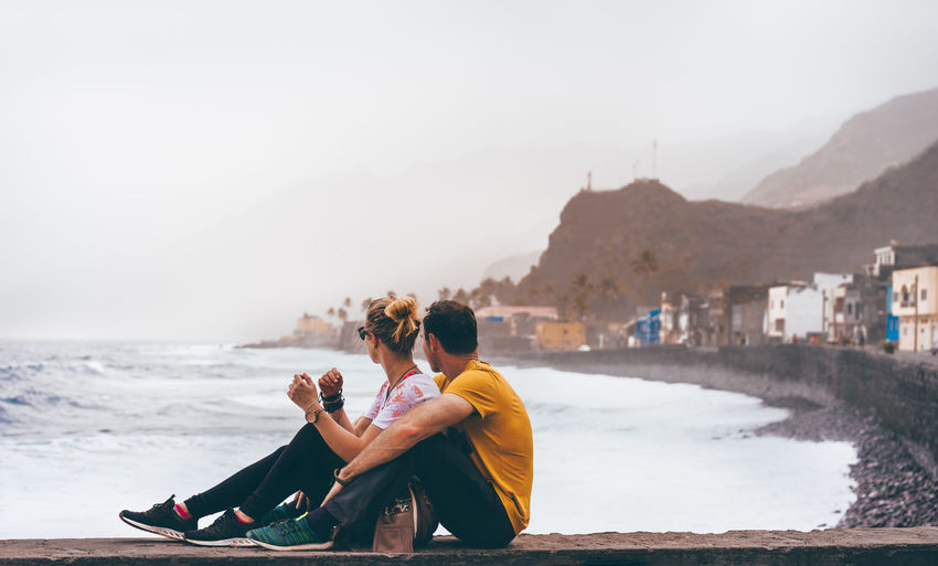 Side view of couple sitting by sea against sky