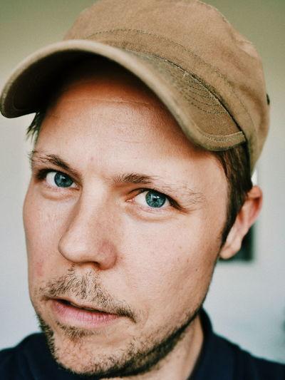 Close-Up Portrait Of Mid Adult Man Wearing Cap