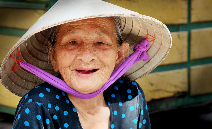 Portrait Of Smiling Senior Woman Wearing Asian Style Conical Hat