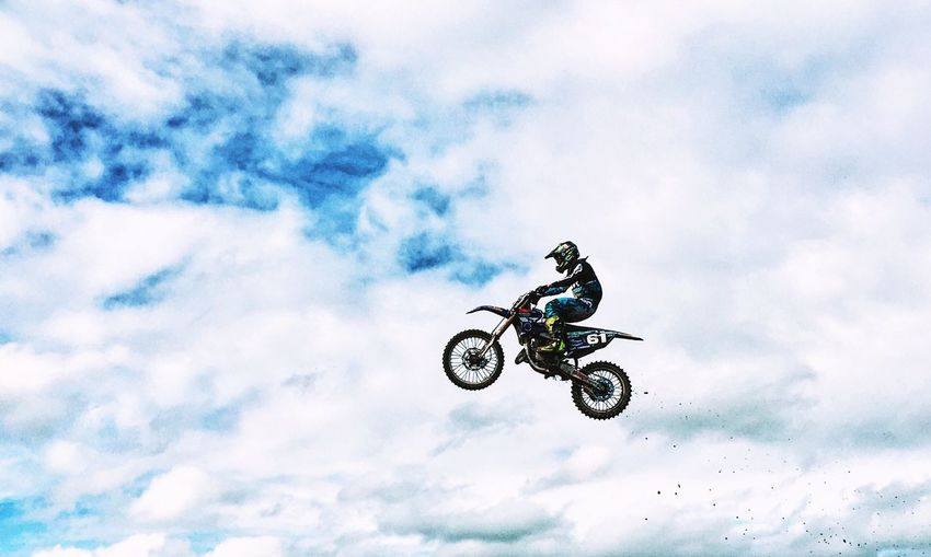 Low angle view of man riding motorcycle against sky