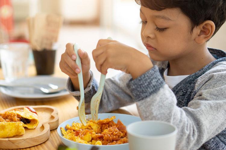 Close-up of boy eating food sitting at restaurant
