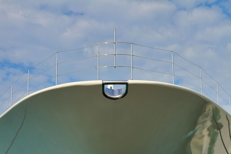 Low angle view of metallic ship structure against sky