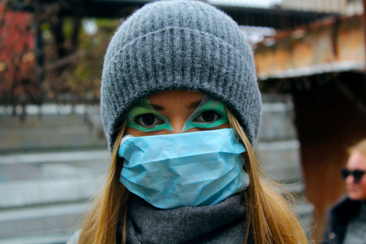 Close-up portrait of young woman wearing knit hat and surgical mask