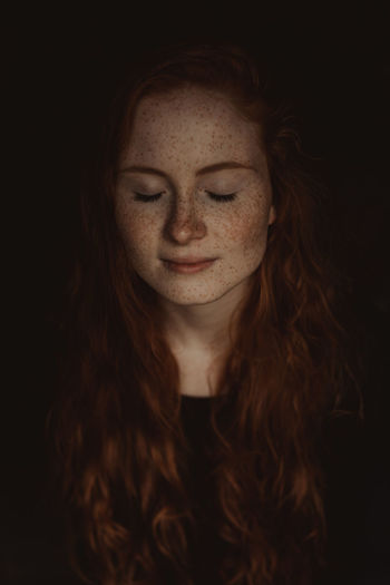 Close-up of young woman with freckles on face against black background