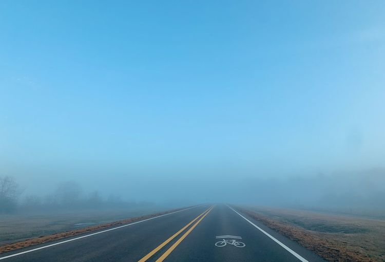 Road disappearing amidst fog during winter