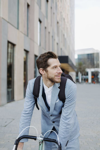 Young man looking away in city