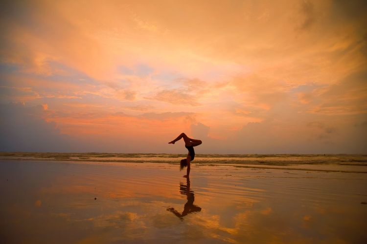 Silhouette Teenage Girl Doing Handstand At Beach Against Cloudy Sky During Sunset