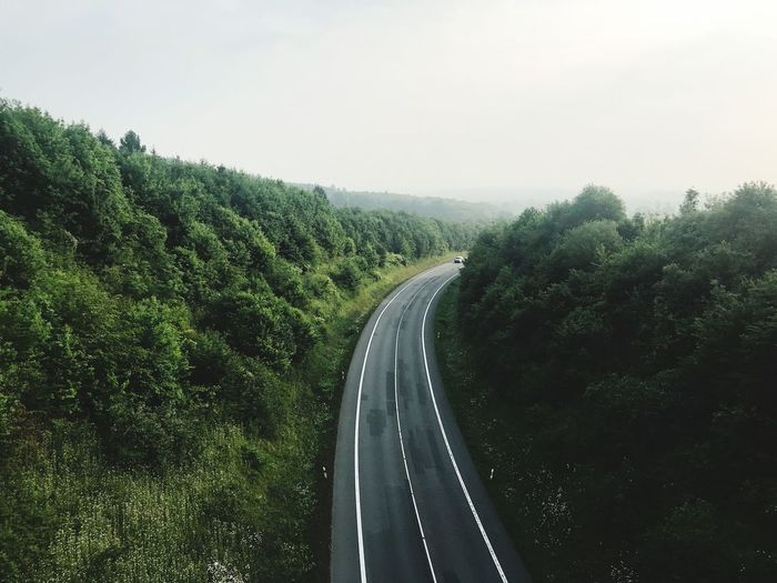 High angle view of empty road amidst trees against sky