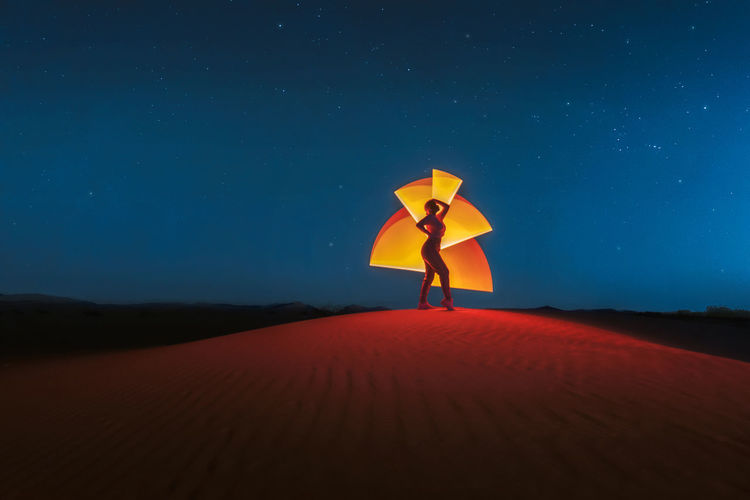 Full length of woman standing on sand dune against sky at night