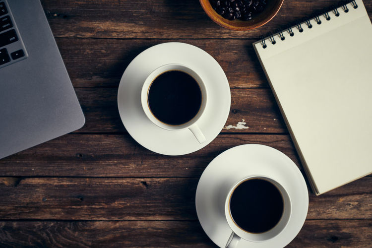 Directly above shot of coffee cups with laptop on table