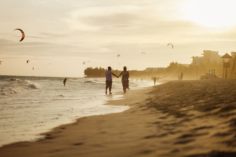 Rear view of couple walking on beach against sky at sunset