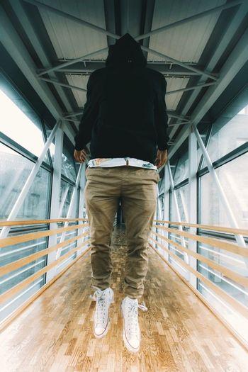 Rear View Of A Man Walking On Footbridge