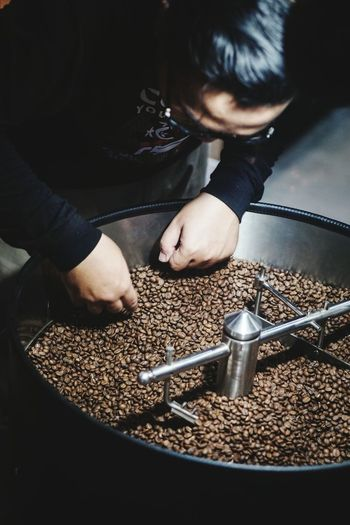 High angle view of man picking roasted coffee beans from container