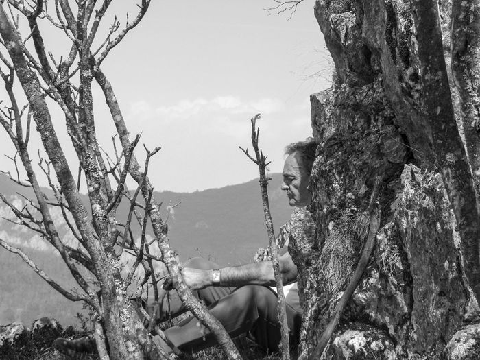 Side view of woman on tree trunk against sky