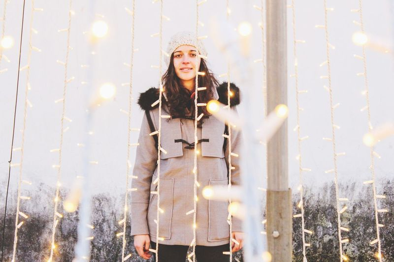 Portrait of woman standing amidst illuminated string lights in winter