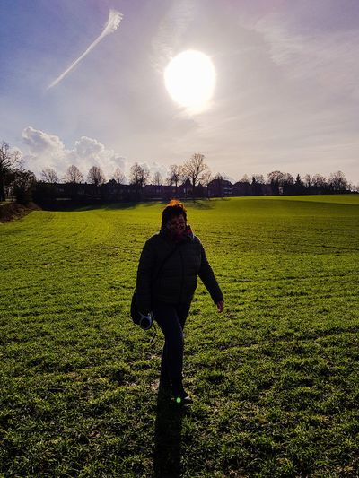 Woman standing on field against bright sun